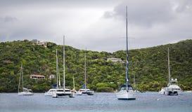Anchored yachts in the tropics. Several luxury catamarans and sailboats anchored along shore of an island Royalty Free Stock Photo