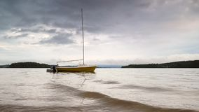 Anchored yellow sailing boat on dark evening Lipno lake. Lazy waves swing