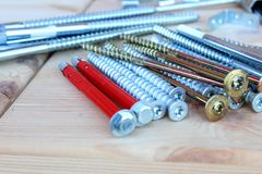 Anchors, screws and bolts. Of different lengths and shapes on wooden boxes royalty free stock image