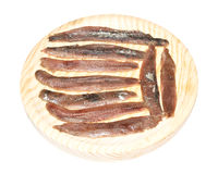Anchovies Fillets. Group of many salted anchovies fillets on wooden plate. Isolated on white Stock Photos