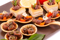 Anchovies in pastries. Lemon, tomato and basil on brown plate Stock Images