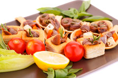 Anchovies in pastries. Lemon, tomato, lettuce and basil on brown plate Royalty Free Stock Photography