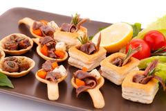Anchovies in pastries. Lemon, tomato, lettuce and basil on brown plate Royalty Free Stock Photos