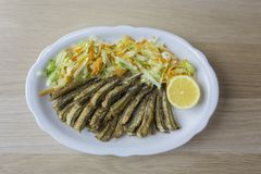Anchovy backed on plate with salad and lemon. Fried anchovy with salad and lemon on a white plate Royalty Free Stock Photography