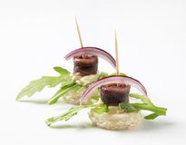Anchovy canapes. Garnished with leaves of arugula Stock Photos