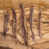 Anchovy fillets on wood. Anchovy fillets on an olive wood background Stock Photos