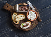 Anchovy and goat cheese sandwich on rustic wooden board. On dark wooden background Stock Images