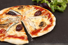A anchovy pizza. On a slate plate with oil and vinegar dressing Royalty Free Stock Photo