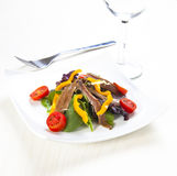 Anchovy salad. Fresh salad with fish on a table Royalty Free Stock Images
