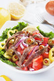 Anchovy salad. With olives, tomato, onion and pepper Stock Photo