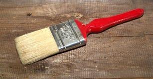 Anchura de la brocha 2 pulgadas con una manija roja en un fondo de madera fotos de archivo