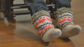 Ancião agradável em botas feitas malha na cadeira de balanço filme