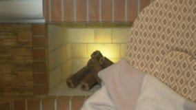 Ancião atrativo na cadeira de balanço perto da chaminé filme