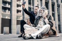 Ancião cinzento-de cabelo entusiasmado que está extremamente feliz com dinheiro imagem de stock