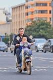 Ancião com o neto na e-bicicleta, Kunming, China Fotografia de Stock Royalty Free