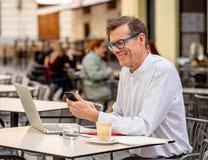 Ancião de sorriso que verifica o telefone esperto ao trabalhar no computador na cafetaria do ar livre do terraço nos sêniores que imagens de stock royalty free
