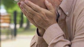 Ancião deprimido só que senta-se no banco, pensando tristemente sobre a vida e o grito filme