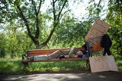 Ancião desabrigado no banco no parque da cidade Foto de Stock