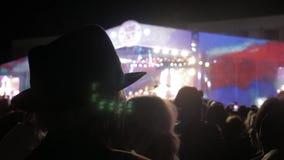 Ancião em um chapéu em um concerto multidão no concerto - festival de música do verão Multidão do concerto que atende a um concer vídeos de arquivo