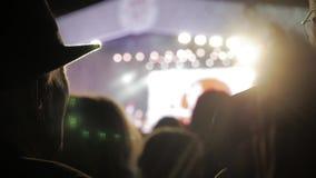 Ancião em um chapéu em multidão no concerto - festival de música do verão Ajuste a multidão que atende a um concerto, silhuetas d vídeos de arquivo