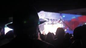 Ancião em um chapéu em multidão no concerto - festival de música do verão Ajuste a multidão que atende a um concerto, silhuetas d filme