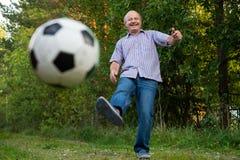 Ancião nos anos setenta que retrocedem uma bola de futebol no campo de jogos foto de stock royalty free