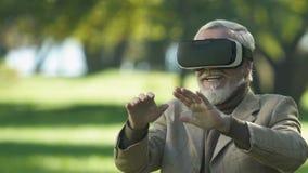 Ancião nos auriculares da realidade virtual que jogam o jogo do simulador, tecnologia moderna video estoque