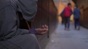 Ancião pobre com a vara no djellaba que implora pelo dotation com mão esticada na rua perto da mesquita em Fes filme