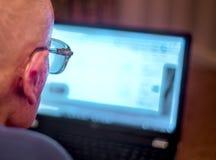 Ancião que aprende sobre o Internet que consulta, usando um laptop para verificar seus portfólios de parte, Hampshire, Inglaterra fotografia de stock