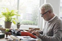Ancião que datilografa em uma máquina de escrever fotos de stock