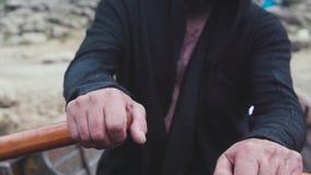 Ancião que enfileira remos no barco de madeira estoque O ancião com barba e a tatuagem na caixa navegam rapidamente da costa no b imagens de stock royalty free