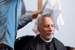 Ancião que está sendo limpado com a toalha pelo barbeiro Fotos de Stock Royalty Free