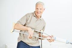 Ancião que joga Air Guitar com muletas Imagem de Stock