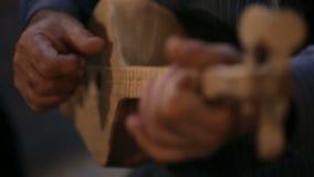 Ancião que joga o instrumento de música Georgian de madeira da corda, concerto popular da cultura video estoque