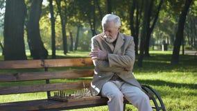 Ancião que senta-se no banco no parque apenas e que joga a xadrez, benefícios de aposentadoria vídeos de arquivo