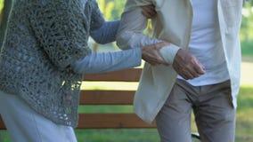 Ancião que tem a dor nas costas, problemas de saúde de envelhecimento, esposa que apoia o marido doente filme