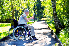 Ancião que tenta levantar-se da cadeira de rodas imagens de stock