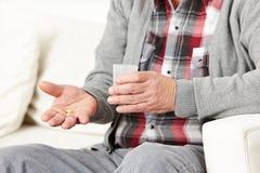 Ancião que toma comprimidos com água imagem de stock royalty free