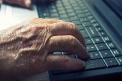 Ancião que usa o caderno Imagem de Stock Royalty Free