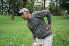 Ancião superior asiático que tem a dor nas costas imagem de stock