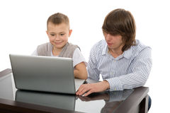 Anciano y hermanos menores para una computadora portátil Fotos de archivo