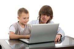 Anciano y hermanos menores para una computadora portátil Foto de archivo