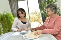 Ancianos de ayuda del ayudante de Homecaring con papeleo fotos de archivo libres de regalías