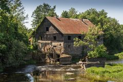 Ancient abandoned water mill surrounded by beautiful nature. House built of stone and wood, exterior walls and dilapidated bridge. On river is reflection of royalty free stock images