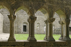 Ancient Abbey Cloisters. The inner courtyard of an ancient abbey in the village of Cong in the Irish countryside. This view, from under a covered walkway, shows stock photo