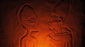 Ancient Alien Wall Carving Lit Up Inside Tomb. Egyptian wall art showing a pharaoh and alien creature stock footage