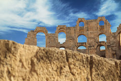 Ancient Amphitheater. Ancient ruined Amphitheater in front of blue cloudy sea with stone brick in foregorund Royalty Free Stock Photos