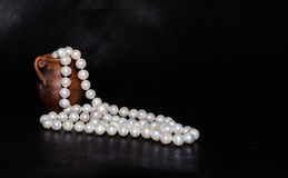 Ancient amphora and pearls over black Stock Images