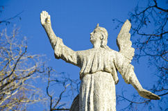 Ancient angel on sky background Stock Photo