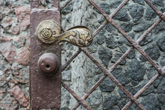 Ancient antique bronze door with iron chain knob. Royalty Free Stock Photos